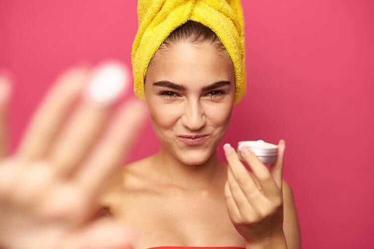Mujer con turbante amarillo enseñando su crema antiarrugas