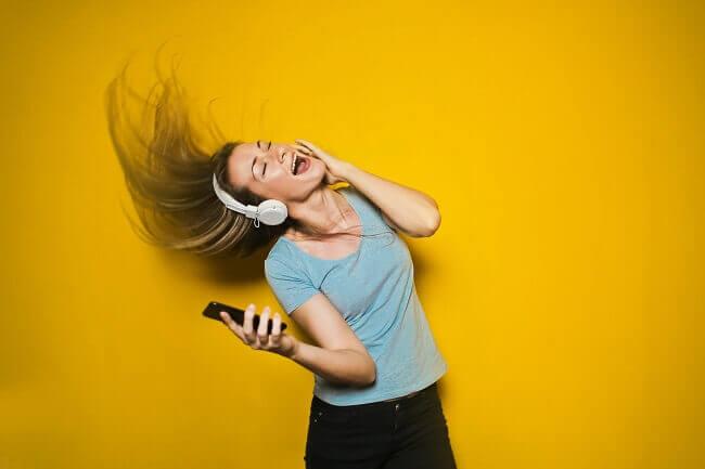 Mujer joven con auriculares de diadema escuchando musica en streaming